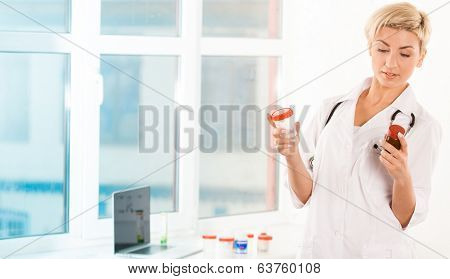 Portrait of a young doctor showing pills near the window
