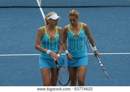 KUALA LUMPUR - APRIL 19, 2014: Olga Savchuk and Lyudmyla Kichenok (white cap) discus tactics in between service in the women's semifinals of the BMW Malaysian Open tennis is Kuala Lumpur, Malaysia.