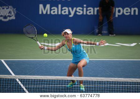KUALA LUMPUR - APRIL 19, 2014: Lyudmyla Kichenok returns in the semifinals of the BMW Malaysian Open in Kuala Lumpur, Malaysia. Partnering Olga Savchuk, they lost to Chan YungJan and Zheng Saisai.