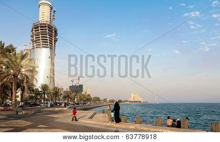 DOHA, QATAR - NOVEMBER 18, 2007: Crowds throng Doha's Corniche after a Red Arrows flying display, while building work goes on at a frantic rate to create the towers of the city's skyline.