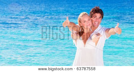 Happy couple on the beach, young family in love spending honeymoon vacation on luxury islands, cheerful active young people having fun at summertime travels, joy of life concept