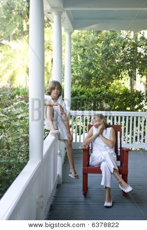 Hermano y hermana relajante en el porche