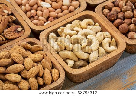 nuts abstract - cashew, pecan, hazelnut, Spanish peanut in wooden bowls