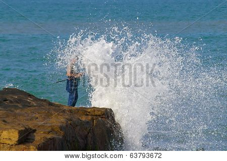 Fisherman caught by the wave.
