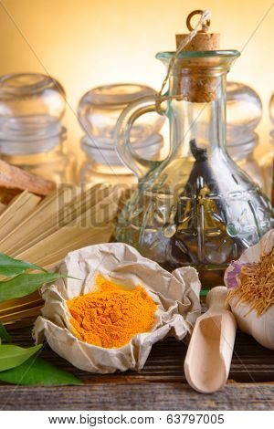 Tumeric powder spice on wooden board with other herbs