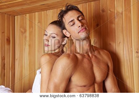 Relaxed couple in hotel sauna leaning on each other