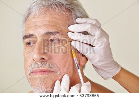Old man getting wrinkles treatment against crow's feet in beauty clinic