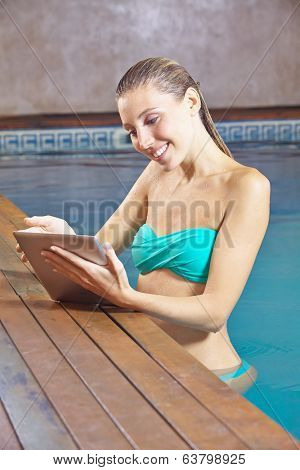 Smiling young woman with tablet PC in a swimming pool in a hotel