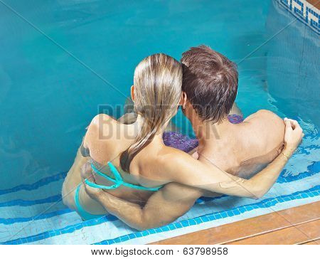Relaxed couple from behind bathing in a swimming pool of a hotel