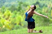 stock photo of filipina  - Beautiful stylish Filipina woman rejoicing in nature kneeling in the green grass in the countryside with her head back and arms outspread in the sunshine with a joyful smile - JPG