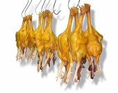 stock photo of giblets  - some plucked and gutted yellow chicken on hooks in front of white back with shadow