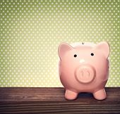 foto of piggy  - Pink piggy bank over green polka dots background - JPG