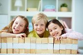 picture of three sisters  - Three little friends with wooden bricks looking at camera - JPG