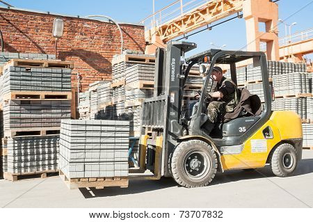 Driver on lift truck loads products of plant