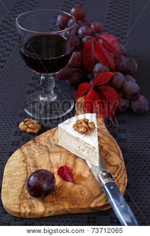 Autumn Composition: Grapes, Scarlet Leaves, Piece Of Cheese And Glass Of Red Wine