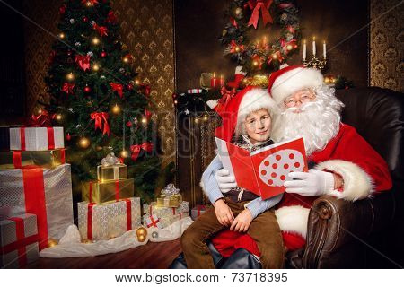 Santa Claus in his everyday clothes in Christmas home d�©cor. Happy little boy helps Santa Claus get ready for Christmas.