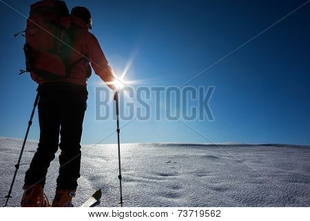 Ski mountaineer walks up hill on a glacier. Rear view, backlight, large copy space on the right. West Alps, Italy, Europe.