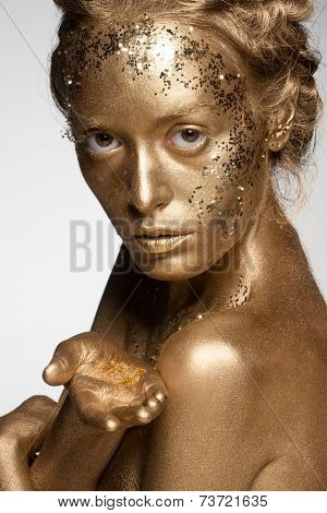 Portrait of beautiful woman with golden makeup and bodyart holding golden sparkles on her palm