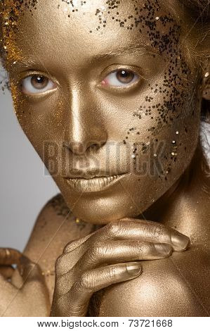 Portrait of beautiful woman with golden makeup and bodyart