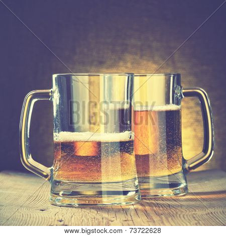 Beer mugs on the wooden table. Instagram style filtred image