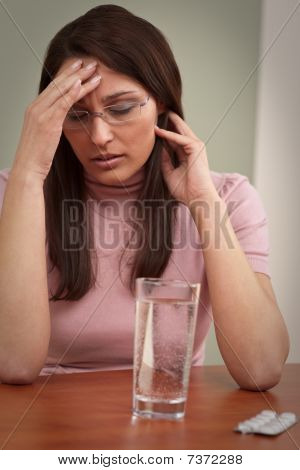 Businesswoman With Headache Take Pill At Office