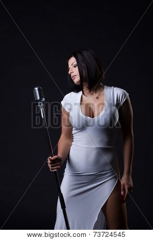 Image of busty slim singer posing in studio