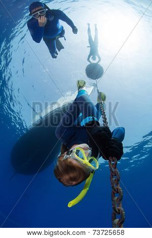 Lady free diver descending along the metal chain using his hands (free immersion). Safety buddy descending close to the athlete