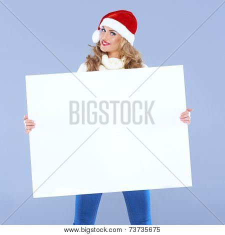 Woman wearing a Santa hat holding a big blank sign smiling