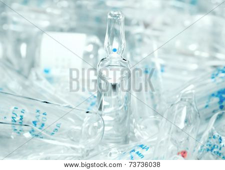 Ampoule Containing Clear Drug With The Background Of The Many Broken Ampoules