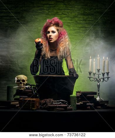 Beautiful witch making the witchcraft over the smoky background. Halloween image
