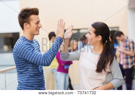 friendship, gesture, education and people concept - group of smiling students outdoors making high five