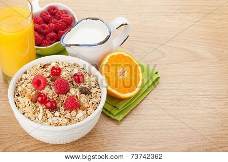Healty breakfast with muesli, berries, milk and orange juice on wooden table with copy space
