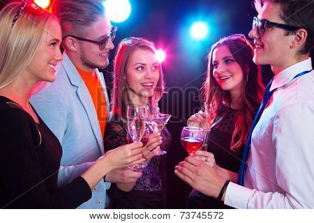 Happy people clinking by glasses with each other