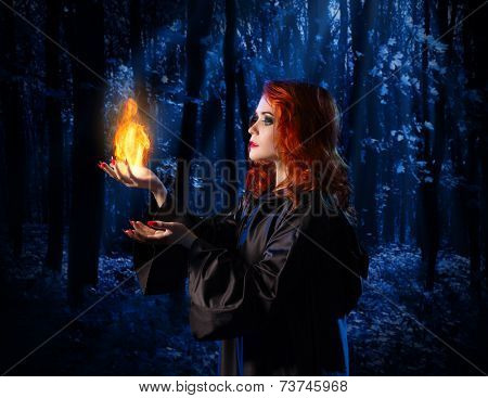 Young witch at night in the moonlight forest with flame