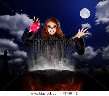 Young witch with red potion and cauldron on night sky background