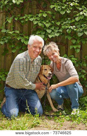 Two happy senior people sitting with a dog in a garden