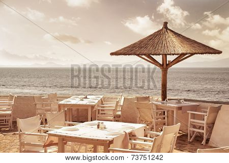 Luxury beach resort, cute white tables, chairs and umbrellas on sandy beach, cozy outdoors cafe, summer vacation concept