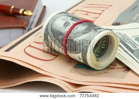Dollars, an organizer and a pen on a newspaper, isolated on white