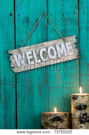 Wood welcome sign by candlelight hanging on antique teal blue rustic wooden door