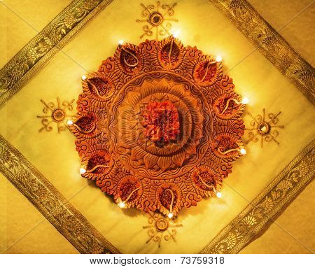 A lit up decorative earthen indian lamp placed on a luxurious fabric