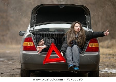 Travelers waiting for assistance in a broken car
