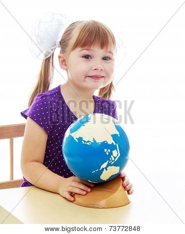 Little girl examines the globe