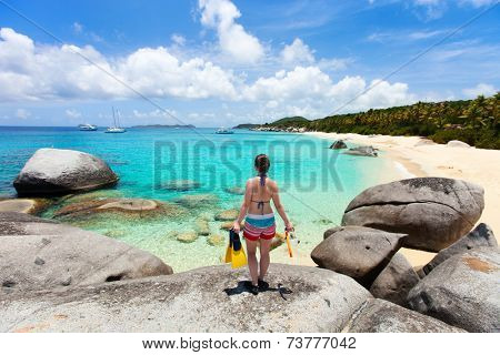 Young woman with snorkeling equipment enjoying view of a tropical beach standing on granite boulder at Virgin Gorda, British Virgin Islands, Caribbean
