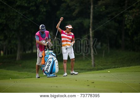 KUALA LUMPUR, MALAYSIA - OCTOBER 11, 2014: Il Hee Lee of South Korea picks her club at of the ninth hole fairway at the KL Golf & Country Club during the 2014 Sime Darby LPGA Malaysia golf tournament.