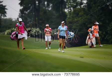 KUALA LUMPUR, MALAYSIA - OCTOBER 11, 2014: LPGA golfers walk on the fairway of the third hole of the KL Golf & Country Club during the 2014 Sime Darby LPGA Malaysia golf tournament.