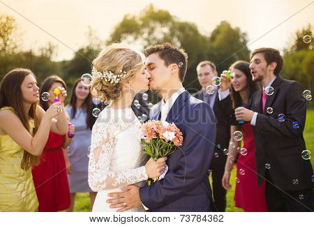 Newlyweds kissing at wedding reception