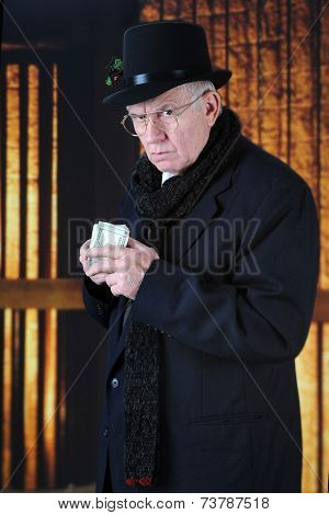 An old Mr. Scrooge in his top hat and scarf scowling at the viewer while holding a fistful of hundred-dollar bills close to his chest.