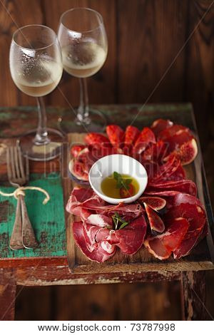wooden board of Assorted Cured Meats, olive oil, fork and glasses of white wine on vintage stool