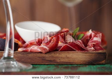 wooden board of Assorted Cured Meats, olive oil and glasses of white wine on vintage stool