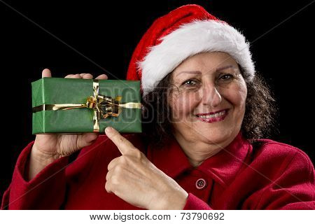 Female Senior Pointing At Green Wrapped Present.